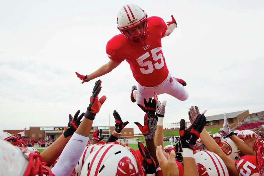 Katy linebacker Nick Bills (55) flies over his teammates before a high school football game against West Brook at  Rhodes Stadium, Saturday, Sept. 17, 2011, in Katy. Photo: Smiley N. Pool, Houston Chronicle / © 2011  Houston Chronicle