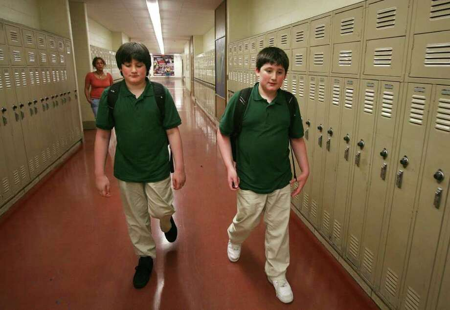 Twins Teagen, left, and Tyler Comeau, 13, walk through the halls at Bassick High School in Bridgeport on Wednesday, September 14, 2011. The brothers, clinically diagnosed with autism but functioning at the level of Asperger's, have long been the targets of bullying. Photo: Brian A. Pounds / Connecticut Post
