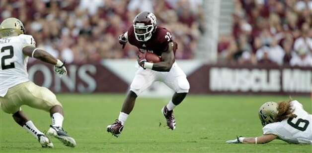 Texas A&M running back Cyrus Gray (32) rushes for a first down as Idaho cornerback Aaron Grymes (6) and safety Quin Ashley (12) defend during the first quarter of an NCAA college football game, Saturday, Sept. 17, 2011, in College Station, Texas. (AP Photo/David J. Phillip) Photo: Associated Press