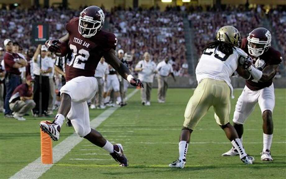 Texas A&M running back Cyrus Gray (32) crosses the goal line for a touchdown as wide receiver Uzoma Nwachukwu, right, blocks Idaho cornerback Matthew Harvey (29) during the second quarter of an NCAA college football game Saturday, Sept. 17, 2011, in College Station, Texas. (AP Photo/David J. Phillip) Photo: Associated Press
