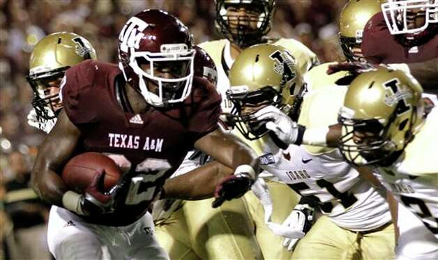 Texas A&M running back Cyrus Gray (32) rushes for a touchdown as Idaho linebacker Tre'Shawn Robinson (51) and cornerback Kenneth Patten (2) defend during the third quarter of an NCAA college football game Saturday, Sept. 17, 2011, in College Station, Texas. (AP Photo/David J. Phillip) Photo: Associated Press