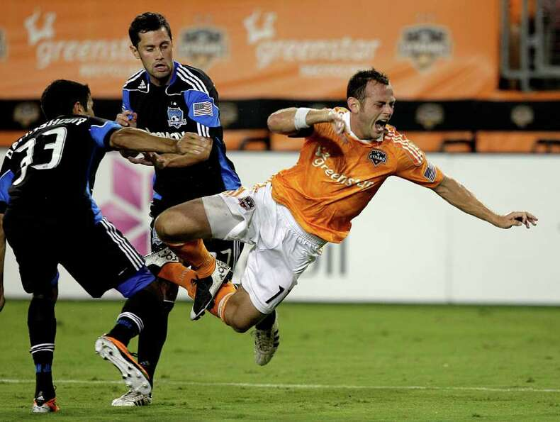 Brad Davis #11 of the Houston Dynamo is tripped up as he attempts to split the defense of Steven Bei