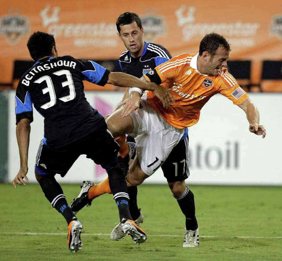 Brad Davis #11 of the Houston Dynamo is tripped up as he attempts to split the defense of Steven Beitashour #33 and Joey Gjertsen #17 of the San Jose Earthquakes in the first half at Robertson Stadium on September 17, 2011 in Houston, Texas. Photo: Bob Levey, Getty / 2011 Getty Images