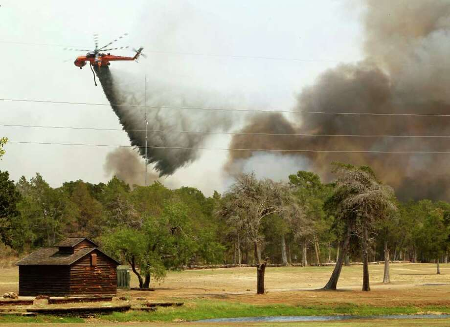 Firefighting helicopters dump water and flame retardant after loading up with water from a pond at Lost Pines Golf Club (Photo by Erich Schlegel/Getty Images) Photo: Erich Schlegel / 2011 Getty Images