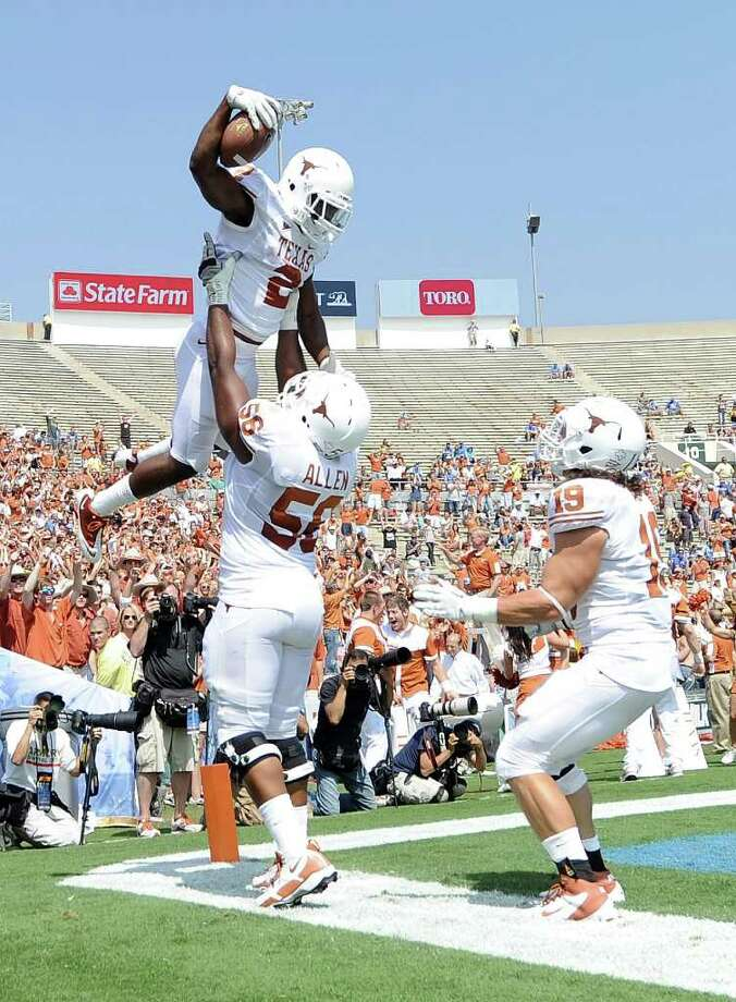 Harry How : getty GROUND CONTROL: Fozzy Whittaker (2) soars above Tray Allen (56) and Blaine Irby after scoring one of the Texas' four rushing touchdowns on a day when the Longhorns ran for 284 yards. Photo: Harry How / 2011 Getty Images