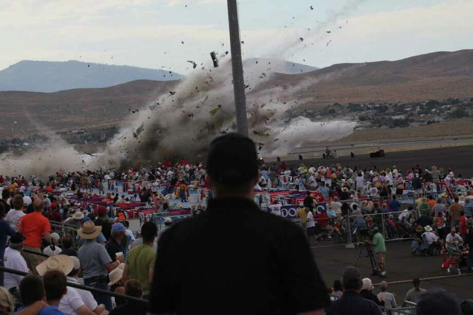 A P-51 Mustang airplane crashes into the edge of the grandstands at the Reno Air show on Friday, Sept. 16, 2011 in Reno Nevada. The World War II-era fighter plane flown by a veteran Hollywood stunt pilot Jimmy Leeward plunged Friday into the edge of the grandstands during the popular air race creating a horrific scene strewn with smoking debris. (AP Photo/Ward Howes) Photo: Ward Howes