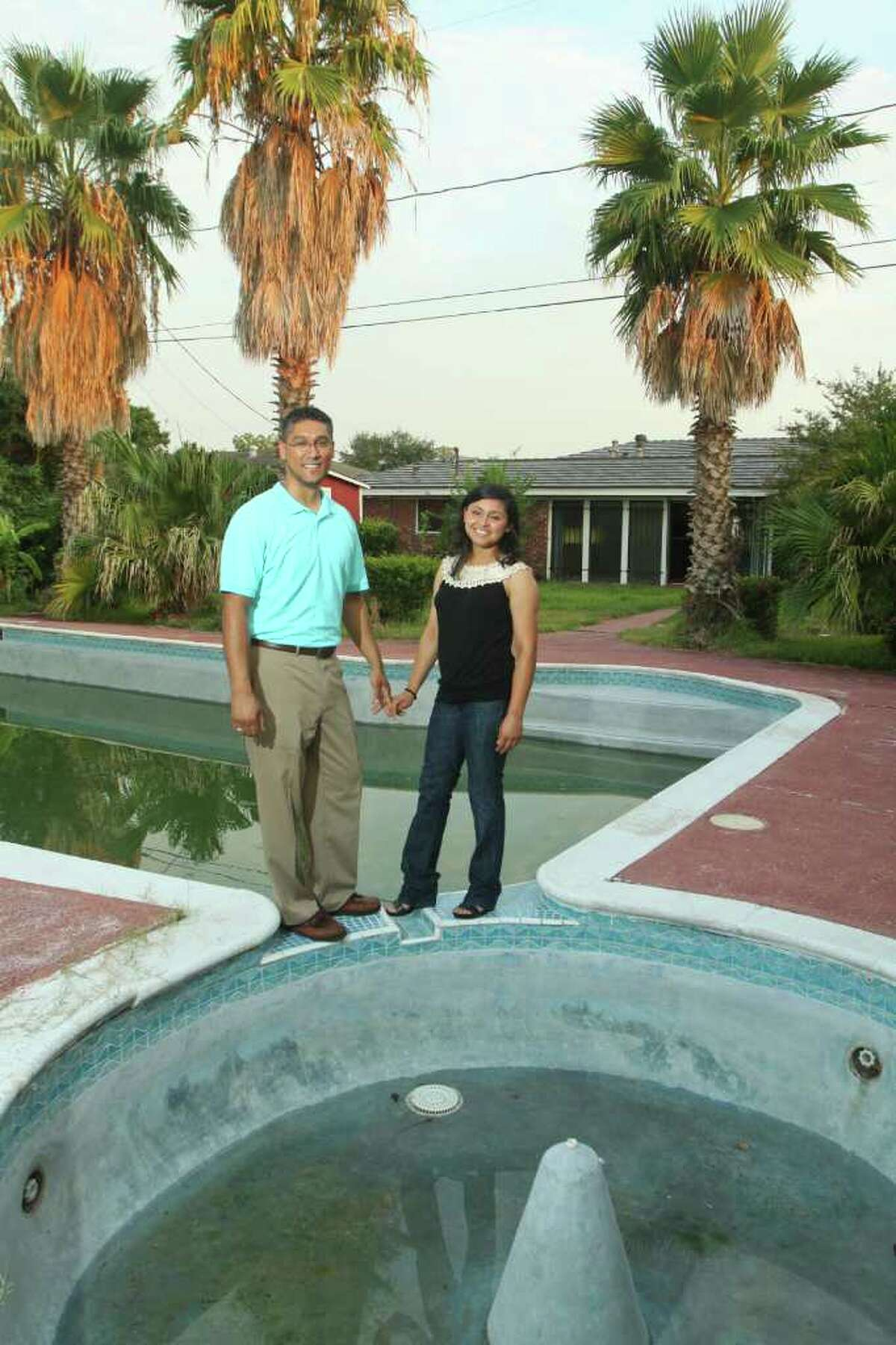 """Sean Evans and Dalia Oliva will be moving into this house in Meadowbrook Freeway. Evans says the house's """"wow factor"""" is a wall of windows overlooking the pool and palm trees."""