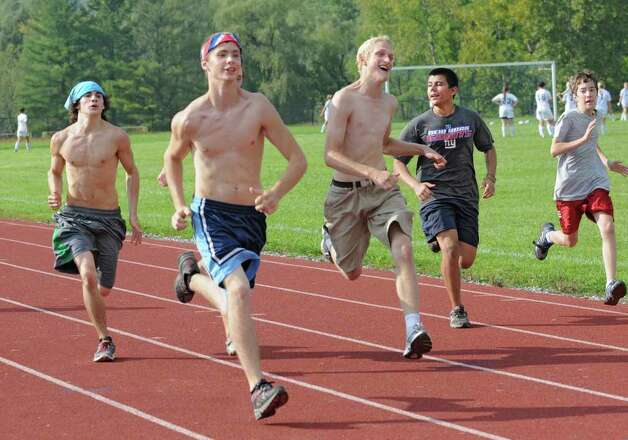 The boys cross country team does laps around the track as girls warm up for a soccer game at Schoharie High School in Schoharie, N.Y. on Sept. 14, 2011. (Lori Van Buren / Times Union) Photo: Lori Van Buren