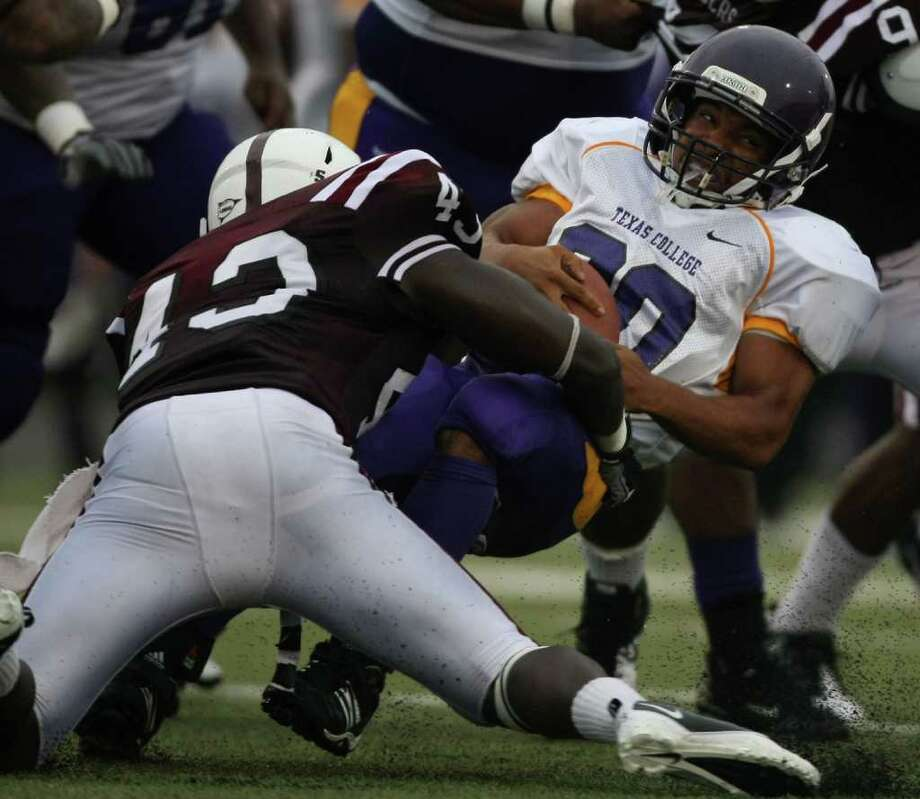 Texas College's Marques Thompson (30) is brought down for a loss by TSU's Samuel Gordy. Photo: Eric Christian Smith, For The Chronicle