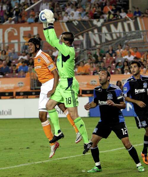Goalkeeper Jon Busch #18 of the San Jose Earthquakes gets to the ball before Calen Carr #3 of the Ho