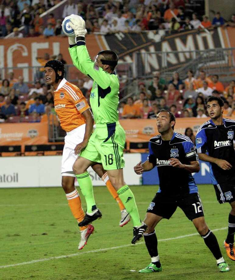 Goalkeeper Jon Busch #18 of the San Jose Earthquakes gets to the ball before Calen Carr #3 of the Houston Dynamo as Ramiro Corrales #12 watches for any rebounds at Robertson Stadium on September 17, 2011 in Houston, Texas. Photo: Bob Levey, Getty / 2011 Getty Images