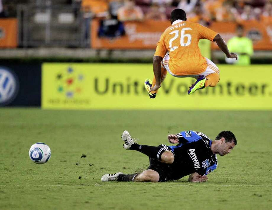Corey Ashe #26 of the Houston Dynamo leaps over a sliding Joey Gjertsen #17 of the San Jose Earthquakes at Robertson Stadium on September 17, 2011 in Houston, Texas. Houston won 2-1. Photo: Bob Levey, Getty / 2011 Getty Images