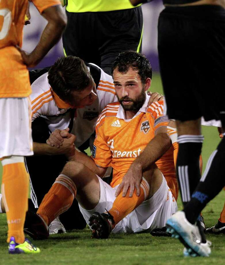 HOUSTON - SEPTEMBER 17:  Adam Moffat #16 of the Houston Dynamo is helped by the training staff after he collided heads with Jacob Peterson #19 of the San Jose Earthquakes in the second half at Robertson Stadium on September 17, 2011 in Houston, Texas. Houston won 2-1. Photo: Bob Levey, Getty / 2011 Getty Images