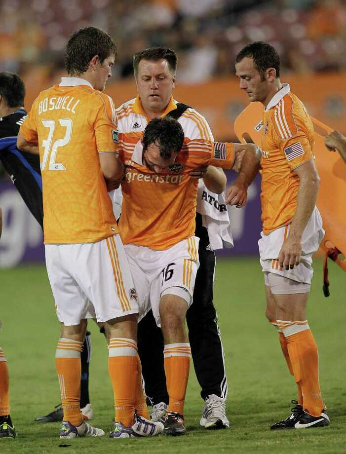 HOUSTON - SEPTEMBER 17:  Adam Moffat #16 of the Houston Dynamo is helped by the training staff  along with Bobby Boswell #32 and Brad Davis #11 after he collided heads with Jacob Peterson #19 of the San Jose Earthquakes in the second half at Robertson Stadium on September 17, 2011 in Houston, Texas. Houston won 2-1. Photo: Bob Levey, Getty / 2011 Getty Images