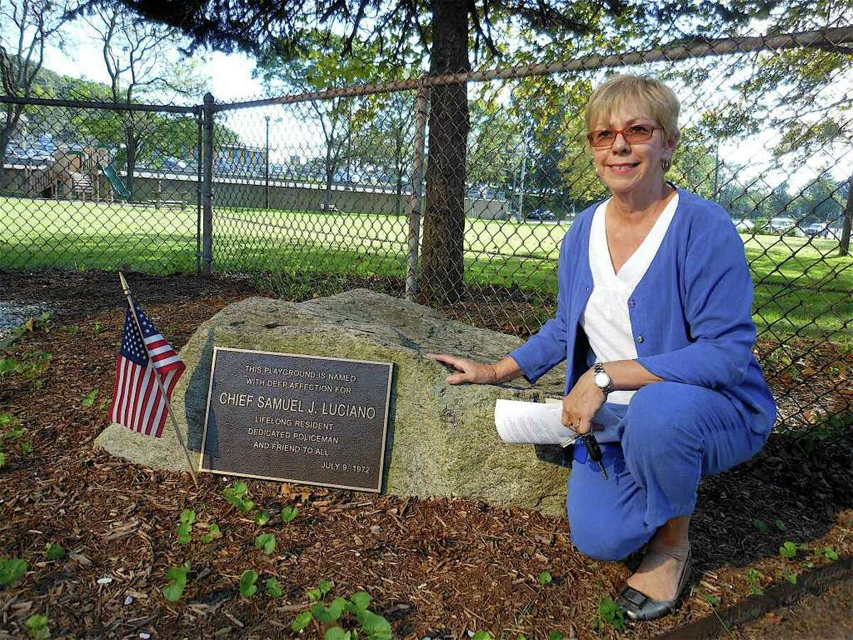 Loretta Santella Hallock kneels beside a plaque dedicated to Sam Luciano, Westport's police chief in the late 1950s and Hallock's first cousin. Luciano Park in the Saugatuck section of town is named after him.