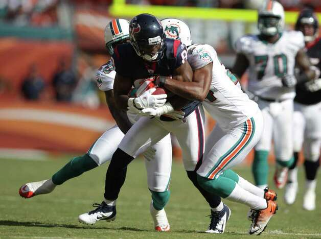 Houston Texans wide receiver Bryant Johnson (89) tries to fight off Miami Dolphins Miami Dolphins free safety Reshad Jones (20)and Miami Dolphins cornerback Sean Smith (24) in the first quarter of a NFL football game, Sunday, Sept. 18, 2011, in Sun Life Stadium in Miami. Photo: Nick De La Torre, Houston Chronicle / © 2011 Houston Chronicle