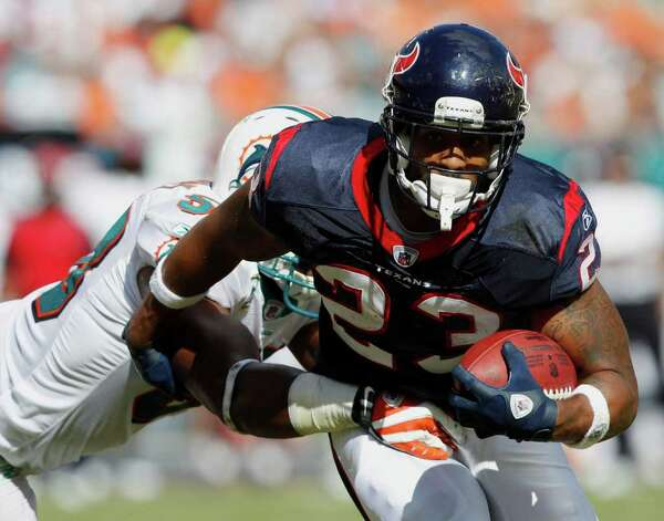 Houston Texans running back Arian Foster (23) runs as Miami Dolphins inside linebacker Karlos Dansby (58) attempts to tackle during the first half of an NFL football game, Sunday, Sept. 18, 2011, in Miami. (AP Photo/Hans Deryk) Photo: Hans Deryk, Associated Press / AP