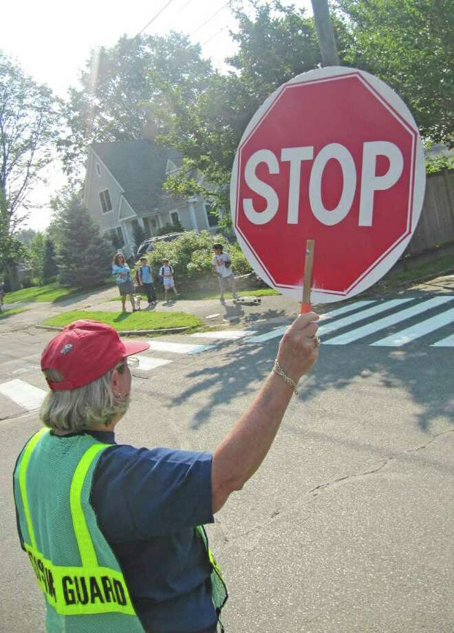 Jenny Devanney, a crossing guard at Roger Sherman Elementary School, holds up a stop sign at the intersection of Fern Street and Beach Road so a mother and three children can safely cross the street.The Fairfield Police said on Tuesday that there is a shortage of crossing guards across town and interested individuals are welcome to apply for the job. Photo: Kirk Lang / Fairfield Citizen