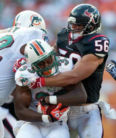 Miami Dolphins running back Daniel Thomas (33) is stopped by Houston Texans inside linebacker Brian Cushing (56) as the Dolphins couldn't score in the second quarter of a NFL football game, Sunday, Sept. 18, 2011, in Sun Life Stadium in Miami. Photo: Nick De La Torre, Houston Chronicle / © 2011 Houston Chronicle