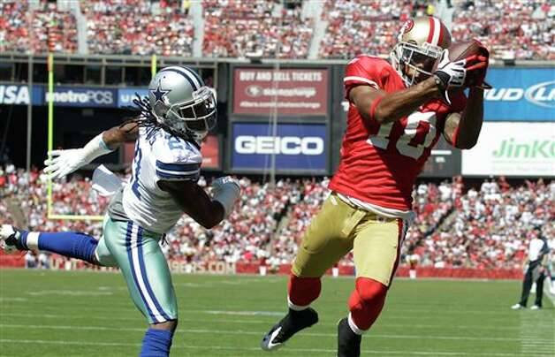 San Francisco 49ers wide receiver Kyle Williams (10) catches a 12-yard touchdown pass from quarterback Alex Smith past Dallas Cowboys defensive back Mike Jenkins (21) in the second quarter of an NFL football game in San Francisco, Sunday, Sept. 18, 2011. (AP Photo/Marcio Jose Sanchez) Photo: Associated Press