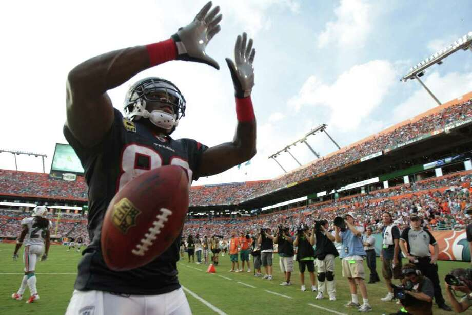 Houston Texans wide receiver Andre Johnson (80) makes a University of Miami sign after scoring a touch down in the fourth quarter of a NFL football game against the Miami Dolphins, Sunday, Sept. 18, 2011, in Sun Life Stadium in Miami. The Texans won 23-13. Photo: Nick De La Torre, Houston Chronicle / © 2011 Houston Chronicle