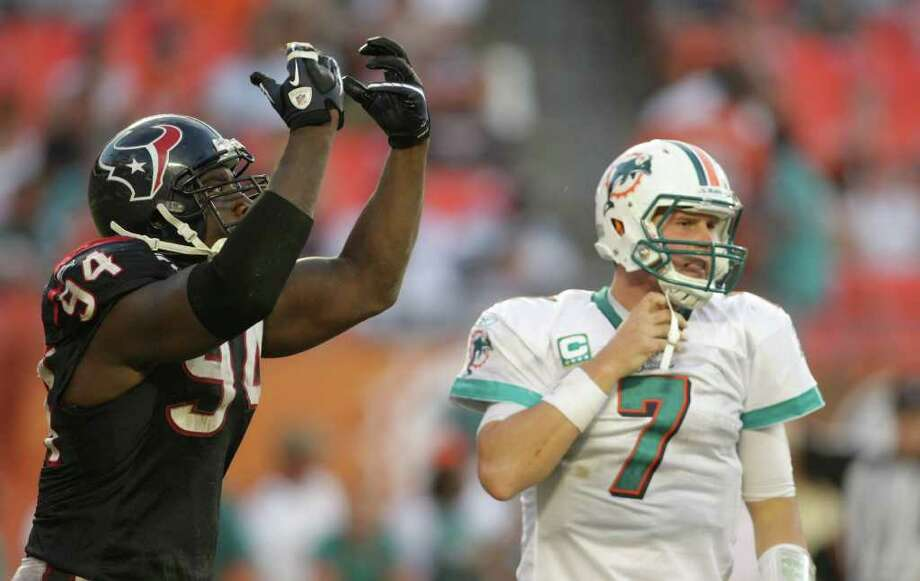 Houston Texans defensive end Antonio Smith (94) does his 'Ninja' act after sacking Miami Dolphins quarterback Chad Henne (7) in the fourth quarter of a NFL football game, Sunday, Sept. 18, 2011, in Sun Life Stadium in Miami. The Texans won 23-13. Photo: Nick De La Torre, Houston Chronicle / © 2011 Houston Chronicle