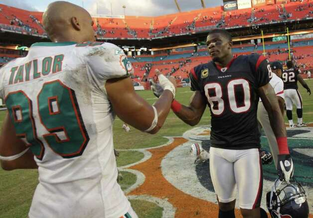 Miami Dolphins linebacker Jason Taylor (99) left, and Houston Texans wide receiver Andre Johnson (80) shake hands after the Texans won 23-13 in a NFL football game, Sunday, Sept. 18, 2011, in Sun Life Stadium in Miami. Photo: Nick De La Torre, Houston Chronicle / © 2011 Houston Chronicle
