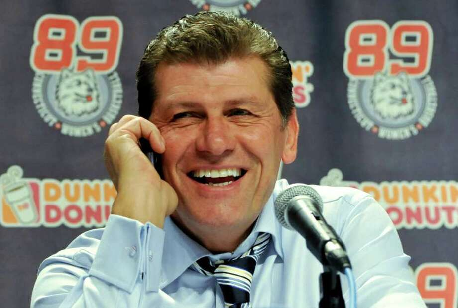Connecticut coach Geno Auriemma takes a congratulatory phone call from President Barack Obama, during a news conference after Connecticut beat Florida State 93-62 in an NCAA college basketball game in Hartford, Conn., Tuesday, Dec. 21, 2010. Connecticut set an NCAA record with 89 consecutive wins . (AP Photo/Jessica Hill) Photo: Jessica Hill, ST / FR125654 AP
