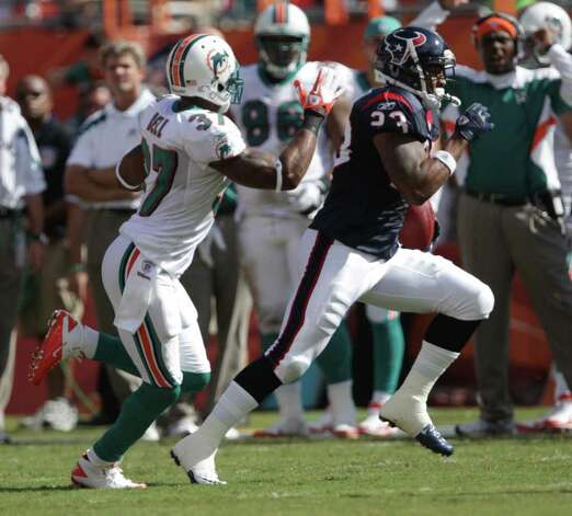Houston Texans running back Arian Foster (23), right, looks to run away from Miami Dolphins strong safety Yeremiah Bell (37) in the first quarter of a NFL football game, Sunday, Sept. 18, 2011, in Sun Life Stadium in Miami. Photo: Nick De La Torre, Houston Chronicle / © 2011 Houston Chronicle