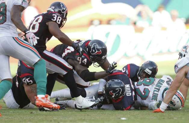 Houston Texans strong safety Glover Quin (29) covers up a fumble he recovered in the third quarter of a NFL football game against Miami Dolphins, Sunday, Sept. 18, 2011, in Sun Life Stadium in Miami. The Texans won 23-13. Photo: Nick De La Torre, Houston Chronicle / © 2011 Houston Chronicle