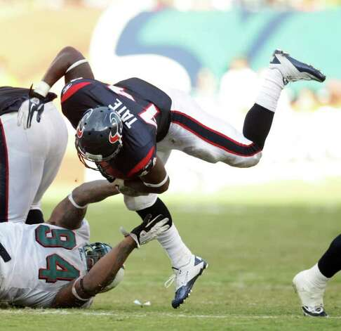 Houston Texans running back Ben Tate (44) tries to run over Miami Dolphins defensive end Randy Starks (94) in the third quarter of a NFL football game, Sunday, Sept. 18, 2011, in Sun Life Stadium in Miami. The Texans won 23-13. Photo: Nick De La Torre, Houston Chronicle / © 2011 Houston Chronicle