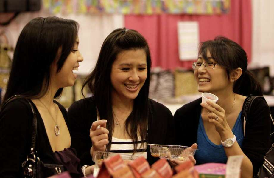 Thuy Nguyen, left, of Katy, and Jenny Luu, and Anna Ng, both of Houston, sample food and drink items Sunday during The Metropolitan Cooking & Entertaining Show at Reliant Center. Photo: Melissa Phillip / © 2011 Houston Chronicle