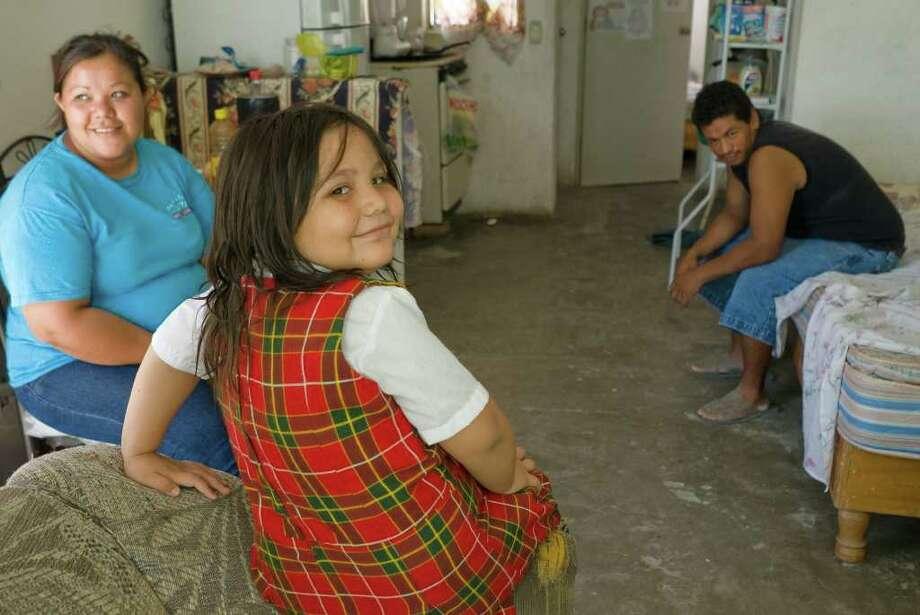 HED: Yuliana Hernandez (mom), Mario Villanueva (Dad) and daughter Barbara Villanueva in their typical house in Colonia San Miguel. Photo: Keith Dannemiller / ©2011 Keith Dannemiller