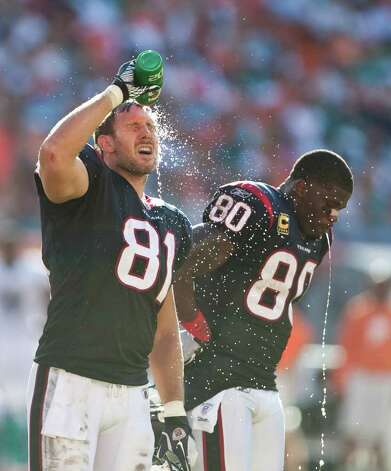 Houston Texans tight end Owen Daniels (81) and Houston Texans wide receiver Andre Johnson (80) try to cool off in the second quarter of a NFL football game against the Miami Dolphins, Sunday, Sept. 18, 2011, in Sun Life Stadium in Miami. Photo: Nick De La Torre, Houston Chronicle / © 2011 Houston Chronicle