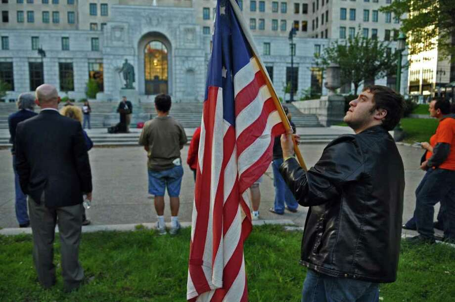 Eddie Alkurabi of Clifton Park, a community organizer with Get Equal, waves a flag while Len Welcome, Executive Vice President of CWA Local 1118 speaks in West Capitol Park during a vigil for the destruction of the middle class,  on Sunday evening Sept. 18, 2011 in Albany, NY.   ( Philip Kamrass / Times Union) Photo: Philip Kamrass / 00014636A