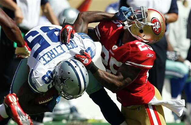 Dallas Cowboys wide receiver Kevin Ogletree (85) stiff arms San Francisco 49ers cornerback Tarell Brown (25) after making a reception in the third quarter of an NFL football game in San Francisco, Sunday, Sept. 18, 2011. (AP Photo/Tony Avelar) Photo: Associated Press