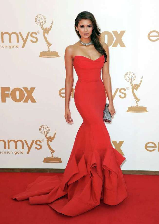 ON FIRE: Nina Dobrev wowed the crowd in a strapless red Donna Karan gown with distinctive pleating at the bottom and on the train. Photo: Kevin Winter / 2011 Getty Images