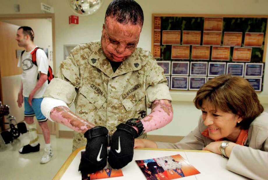Sgt. Merlin German signs photos from his promotion ceremony at Brooke Army Medical Center in 2007 as friend Norma Guerra looks on. German came up with the idea for Merlin's Miracles, a nonprofit that helps families of burn victims. It is headed by Guerra. German, who was severely burned in 2005 by a roadside bomb in Iraq, died in 2008. Photo: Eric Gay/Associated Press / AP