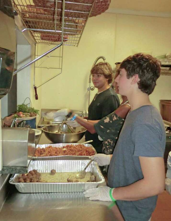 Staples High School students (left to right) Ben Reiser, Kelly Powers (partially hidden) and Rusty Schindler, all members of the school's culinary club, served food at the Gillespie Center on Sept. 9 after preparing the fare one day prior. All of the food was made from ingredients obtained at the Westport Farmers' Market and the high school's gardens. Staples students, the Westport Farmers' market and Sunrise Rotary will provide shelter residents will fresh dinners once a month over the next year. Rotary has committed $1,000 to the effort. Photo: Contributed Photo / Westport News contributed
