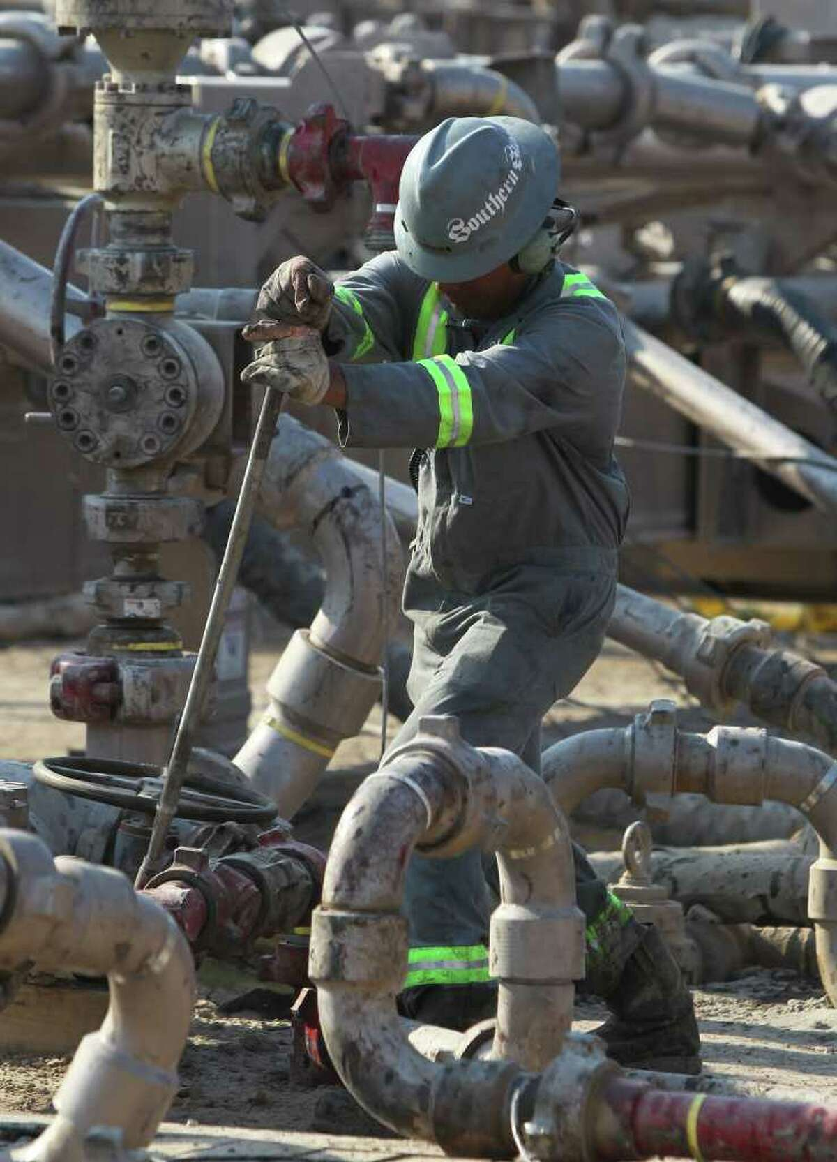 An oilfield employee works at a Talisman Energy fracking site near Cotulla. A reader asks if energy drilling sites (including the Eagle Ford Shale area) have limits placed on them when it comes to water, especially at a time when drought has lowered levels in aquifers and individual wells.