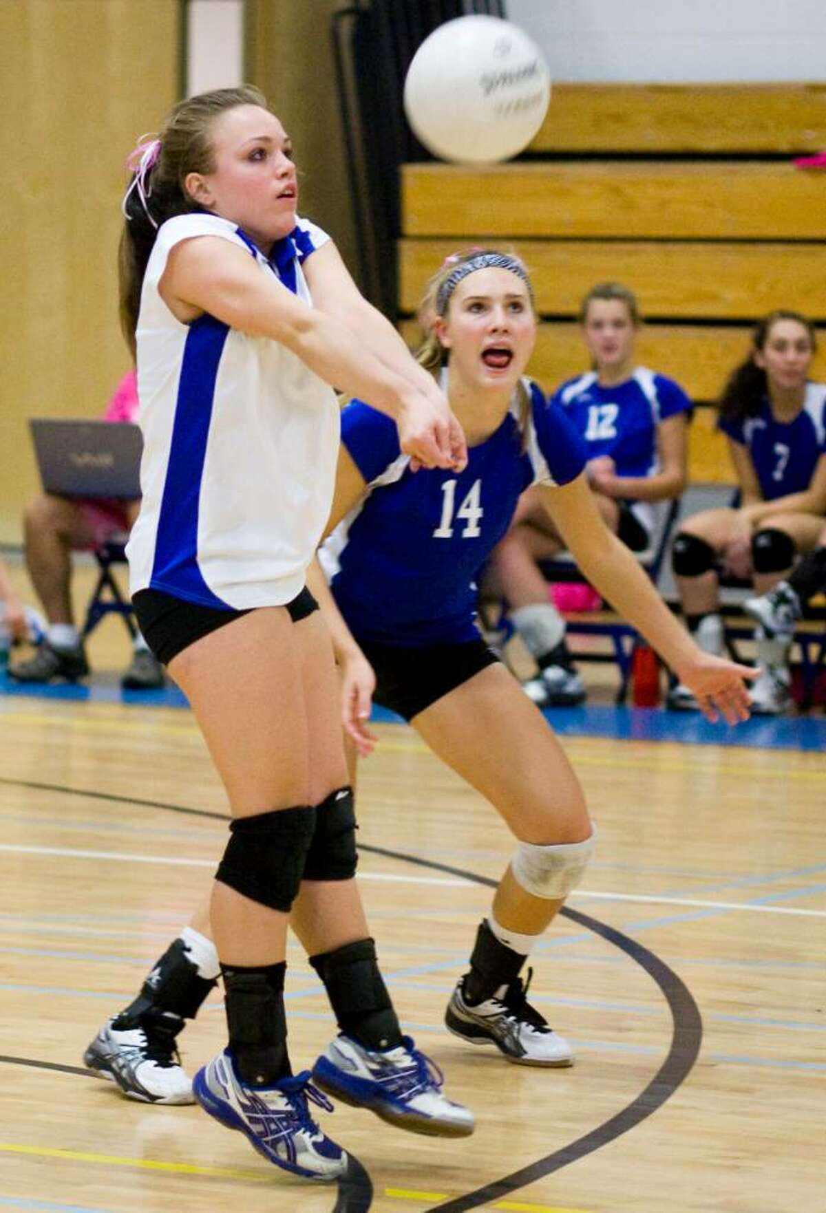 Darien High School's #5 Sarah Suckow, left, plays the ball as she's cheered on by teammate #14 Corinne Sommi, right, during a game against Wilton High School in girls volleyball in Darien.