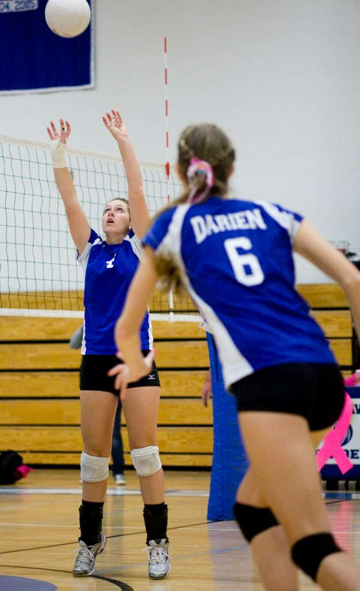 Darien High School's #4 Mackenzie Begley, left, sets the ball as teammate #6 Sarah Gorski, right, runs in from the right during a game against Wilton High School in girls volleyball in Darien.