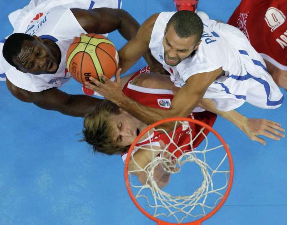 Russia's Andrei Kirilenko, center, challenges for the ball with France's Tony Parker, right, and Florent Pietrus, during their semifinal EuroBasket European Basketball Championship match in Kaunas, Lithuania, Friday Sept. 16, 2011. Photo: Darko Vojinovic/Associated Press / AP