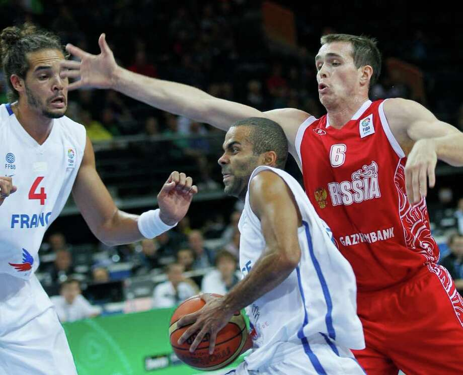 France's Tony Parker, center, challenges for the ball with Russia's Sergey Bykov, right, during their semifinal EuroBasket European Basketball Championship match in Kaunas, Lithuania, Friday Sept. 16, 2011. Photo: Darko Vojinovic/Associated Press / AP