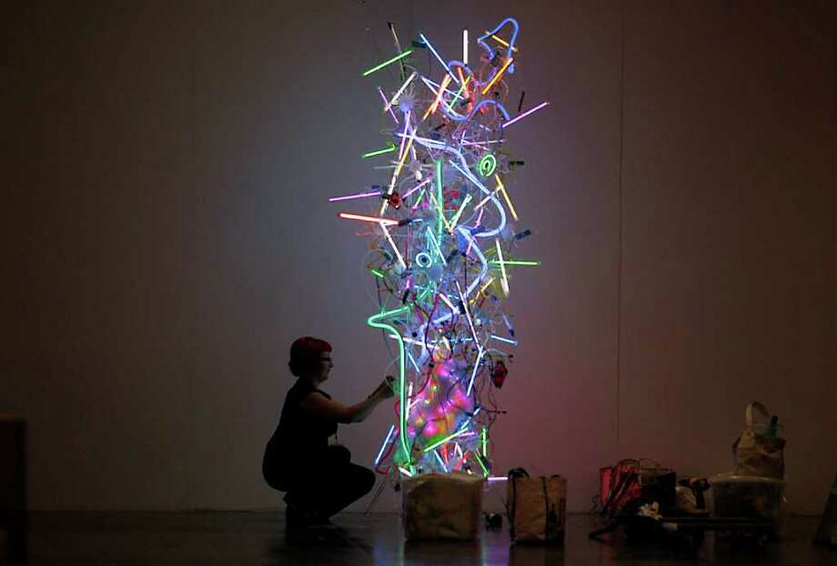 MAYRA BELTRÁN : CHRONICLE PROFITABLE: Adela Andea, assembling her free-standing light sculpture before the Houston Fine Art Fair, landed some commissions and sales during the event. Photo: Mayra Beltran / © 2011 Houston Chronicle