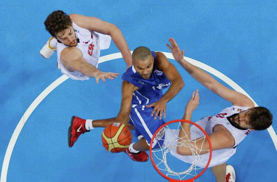 Pau Gasol, left, and Marc Gasol, right, from Spain fight for a ball with Tony Parker, center, from France during the EuroBasket European Basketball Championship gold medal match in Kaunas, Lithuania, Sunday, Sept. 18, 2011. Spain won the match 98-85. Photo: Petr David Josek/Associated Press / AP