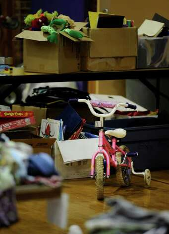 Donations of clothing and children's games and play items are sorted in the ...