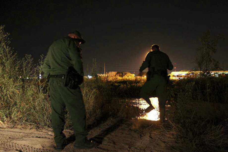 U.S. Border Patrol agents Dan Milian, left, and Joel Sievert look for tracks as they patrol the Rio Grande near McAllen, Texas, Monday, Sept. 19, 2011. Photo: JERRY LARA, Express-News / glara@express-news.net