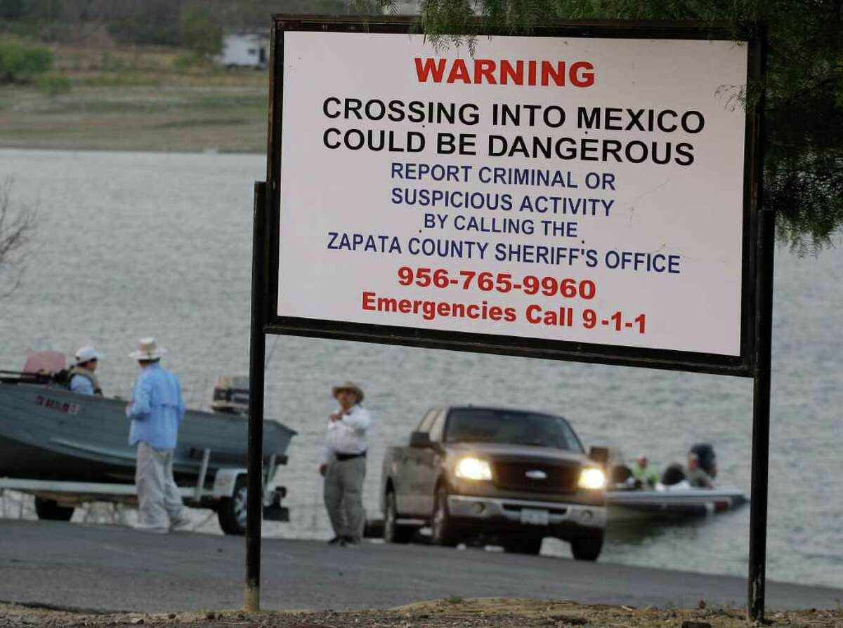 A warning sign is seen at a public boat ramp on Falcon Lake, June 9, 2011 in Zapata, Texas. Tourism dropped off sharply on the dammed section of the Rio Grande that straddles the Texas-Mexico border after Sept. 30, when an American jet-skier was presumably shot and killed by Mexican pirates. The Mexican side of the lake remains marred by drug violence which has even featured shootouts pitting reputed smugglers against the Mexico's navy. But business is picking up in shoreline Texas towns like Zapata, whose economies rely on out-of-towners who like to fish.