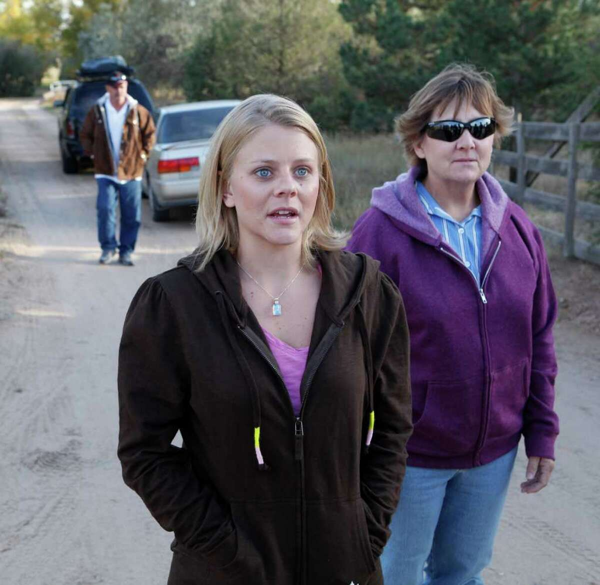 Tiffany Hartley, center, arrives at her parents home in LaSalle, Colo., on Saturday, Oct. 23, 2010, with her mom Cynthia, right, and father Bob Young, left, after riding with them from Texas. Hartley's husband was shot and believed killed while the couple were jet skiing on Falcon Lake last month. David Hartley's body has not been recovered.
